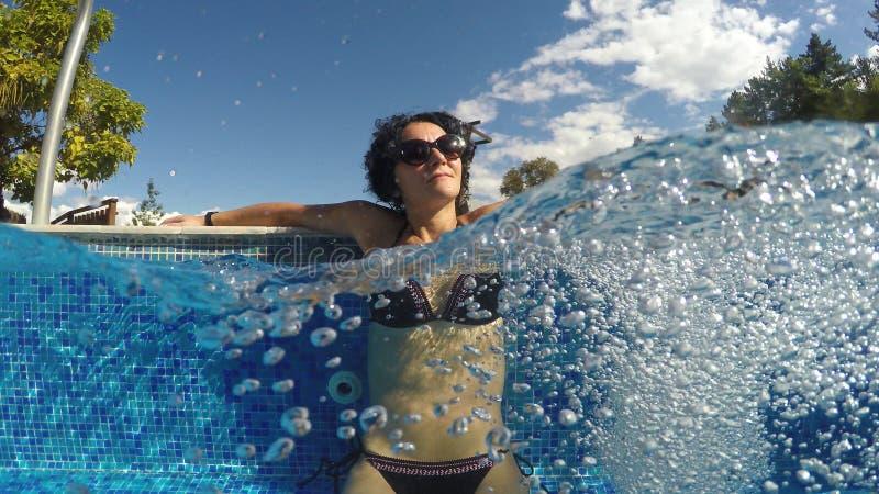 Jovem mulher sensual que relaxa na piscina exterior dos termas imagem de stock royalty free