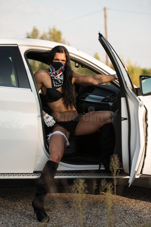Jovem mulher sensual que relaxa no carro fotografia de stock
