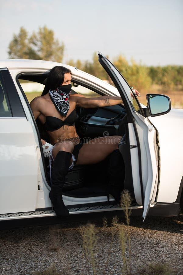 Jovem mulher sensual que relaxa no carro imagens de stock royalty free