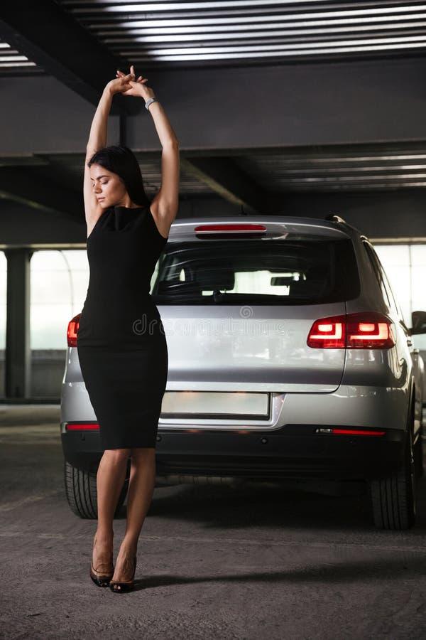 Jovem mulher sensual que stading e que levanta no estacionamento do carro imagens de stock