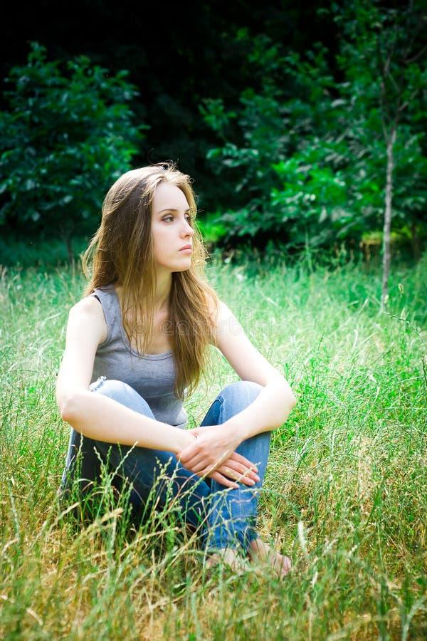 A jovem mulher senta-se, de pernas cruzadas foto de stock royalty free