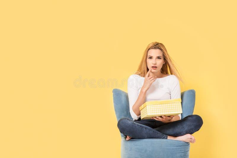 A jovem mulher senta-se na cadeira com giftbox fotografia de stock royalty free