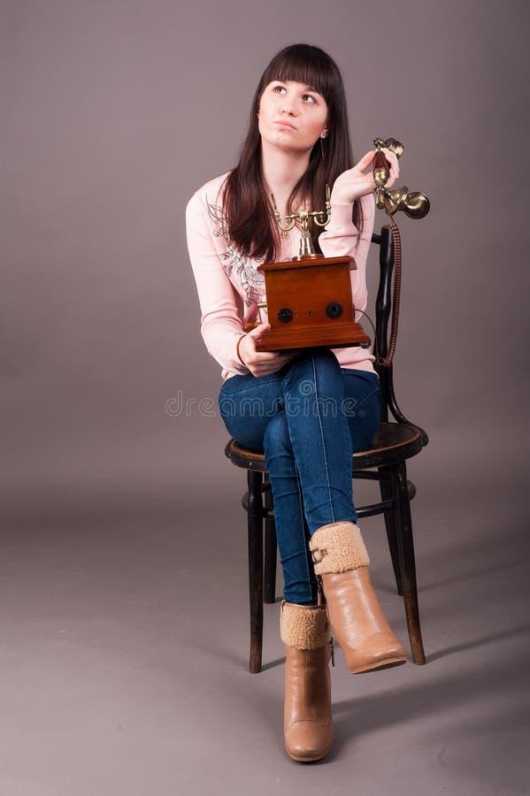 A jovem mulher senta-se na cadeira com telefone do vintage fotos de stock royalty free