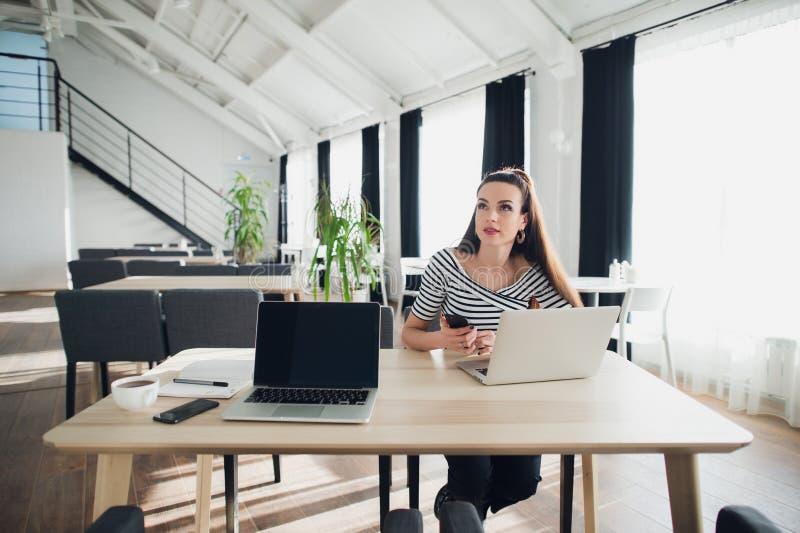 A jovem mulher senta-se na tabela do café usando um portátil e guardando um telefone celular ao olhar afastado com olhar pensativ imagens de stock