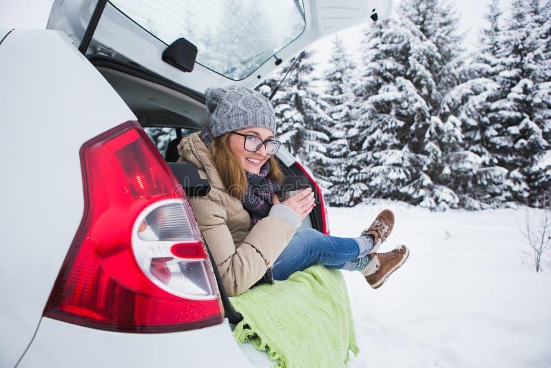 A jovem mulher senta-se no tronco do carro e guarda-se um copo do chá quente foto de stock royalty free