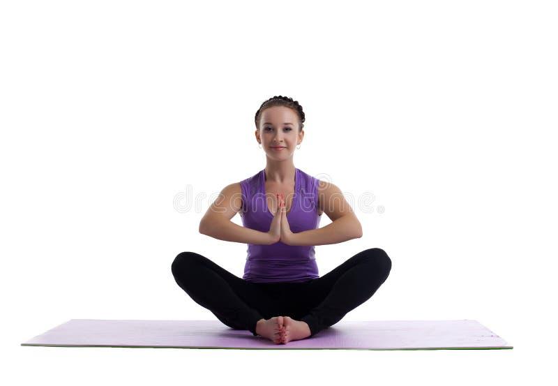 A jovem mulher senta-se nos lotos como o asana da ioga na esteira imagem de stock