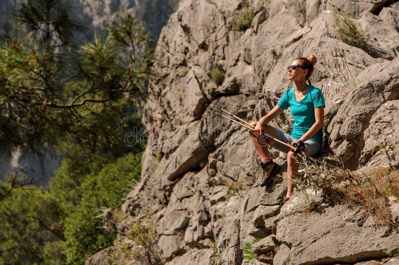 A jovem mulher senta-se sobre a montanha fotografia de stock