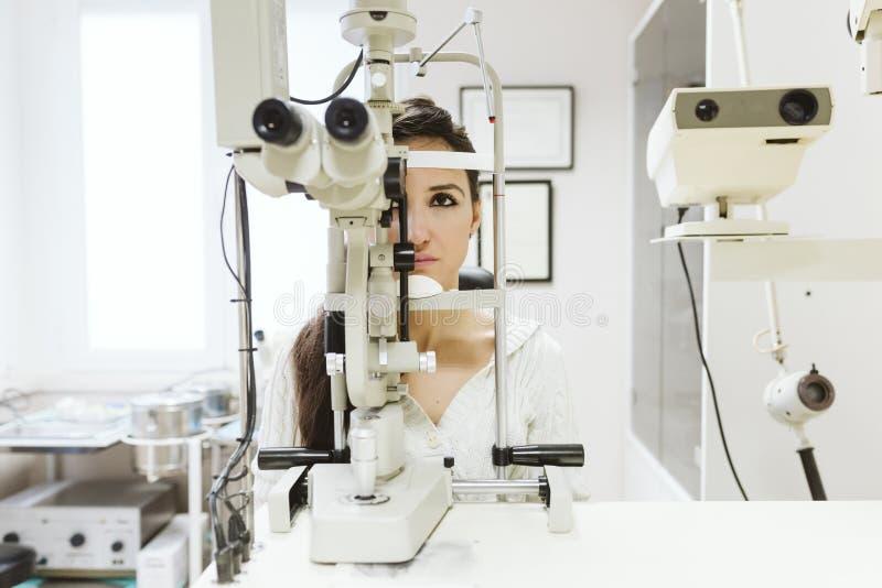 jovem mulher sentada na clínica oftalmologista para que seus olhos fossem examinados por um profissional imagens de stock royalty free