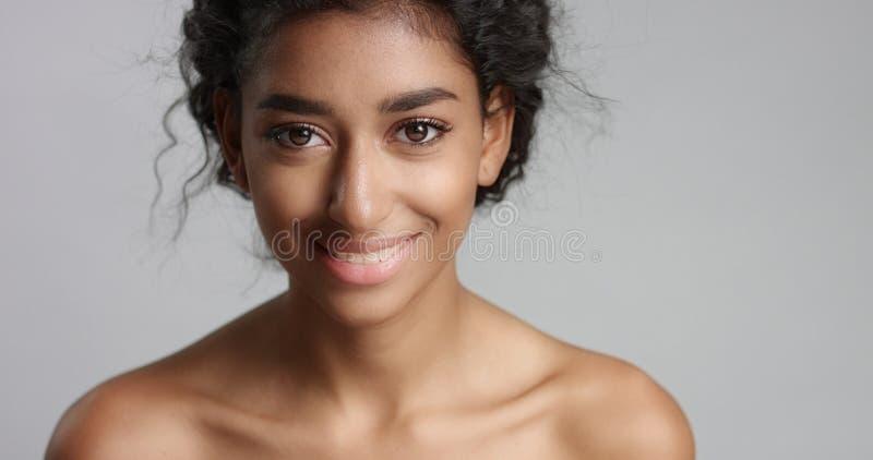Jovem mulher sereno feliz com os olhos ideais verde-oliva bonitos de pele e de pele e de marrom do cabelo encaracolado no estúdio foto de stock royalty free
