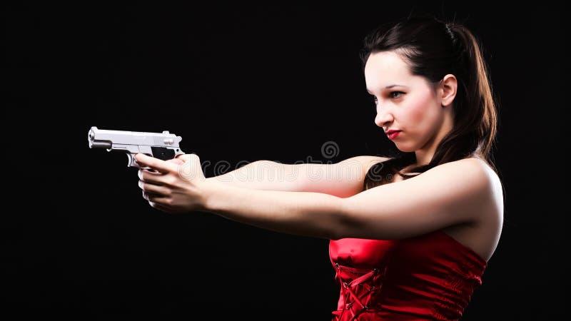 Jovem mulher 'sexy' - arma no fundo preto foto de stock royalty free