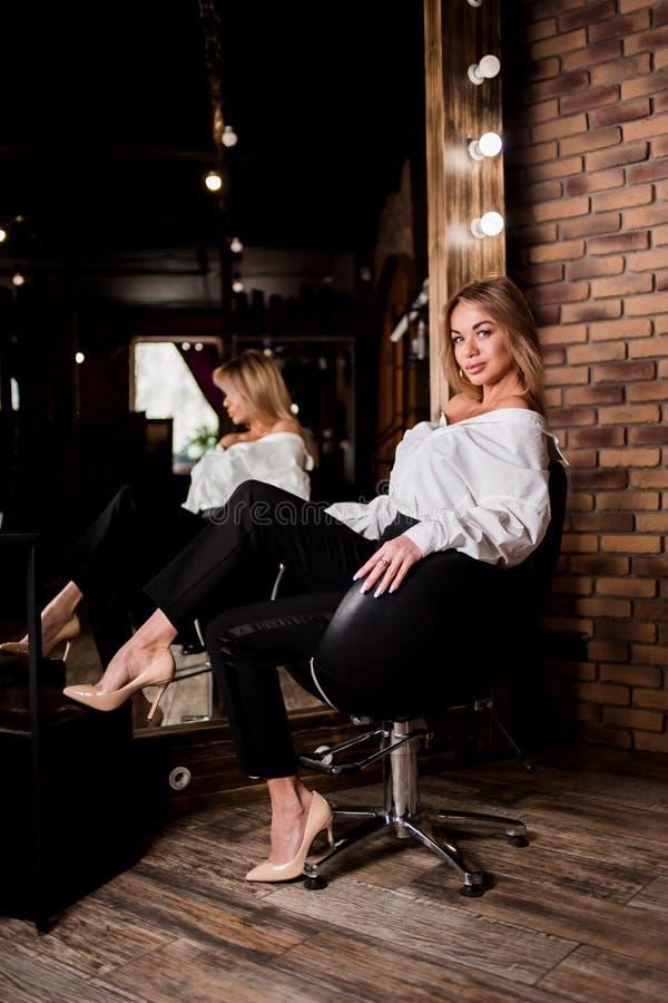 Jovem mulher 'sexy' bonita elegante na camisa branca, calças preta que senta-se na cadeira ao lado do grande espelho Interior do  foto de stock