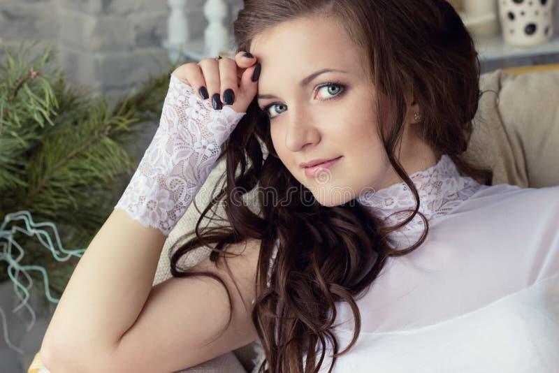 Jovem mulher 'sexy' bonita em um bodysuit branco que senta-se perto da janela em uma cadeira confortável fotografia de stock