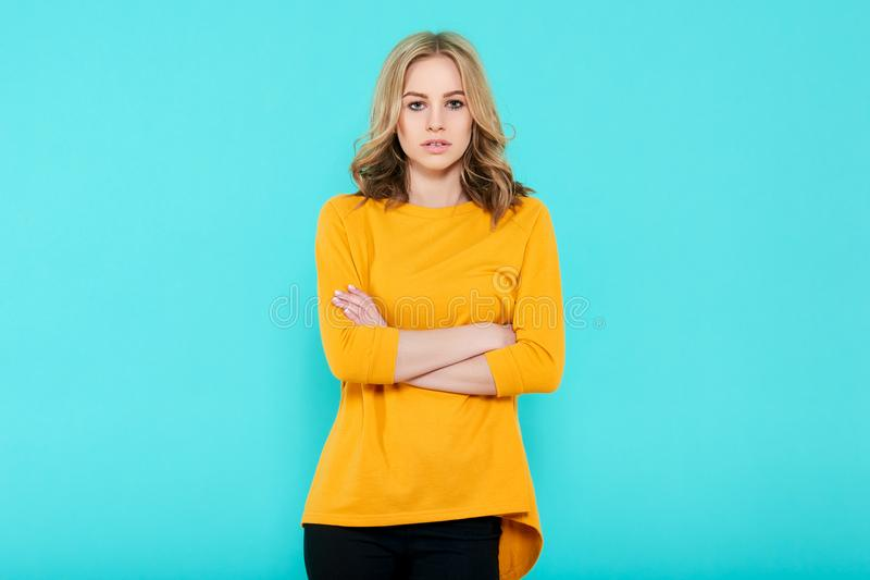 Jovem mulher 'sexy' bonita no retrato superior amarelo brilhante do estúdio no fundo azul pastel Mulher atrativa com braços cruza foto de stock