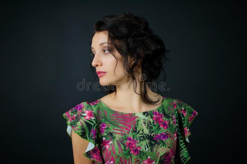 A jovem mulher 'sexy' de surpresa com composição e um penteado elegante levanta no estúdio no fundo preto que veste o vestido ver imagem de stock