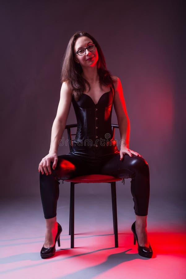 Jovem mulher 'sexy' em um espartilho e látex em uma cadeira fotografia de stock
