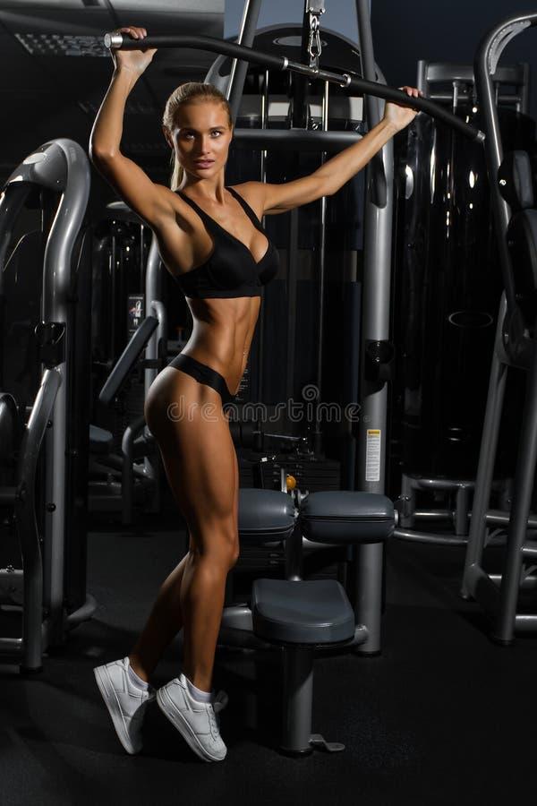 Jovem mulher 'sexy', muscular no roupa interior que levanta contra o gym, figura completa do corpo fotos de stock royalty free