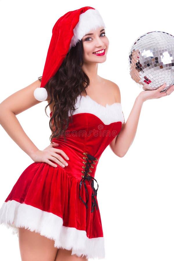 Jovem mulher 'sexy' no desgaste do Natal e chapéu que guarda a bola do disco Isolado no fundo branco fotografia de stock