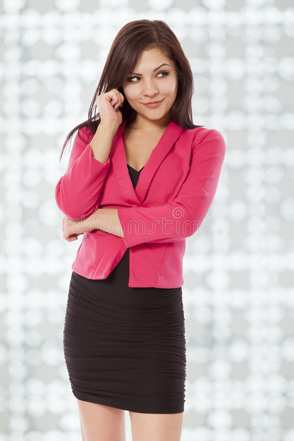 A jovem mulher 'sexy' no equipamento do negócio olha ao lado com um manhoso imagem de stock royalty free