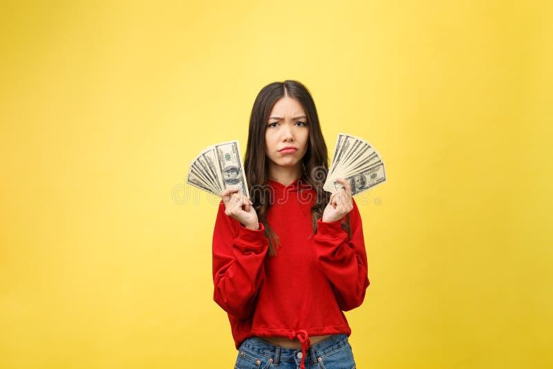 Jovem mulher sobre a parede amarela que mantém dólares forçados com mão na cabeça, chocada com a cara da vergonha e da surpresa,  fotografia de stock royalty free