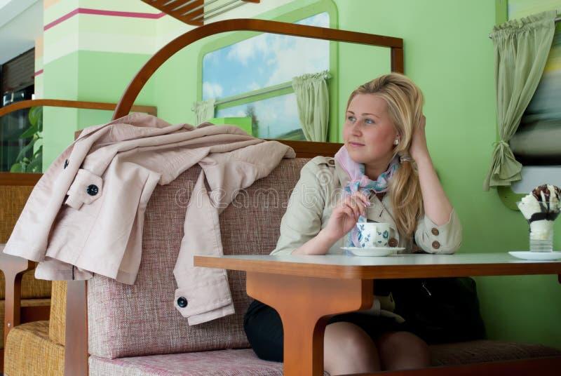 Jovem mulher sonhadora que senta-se em um café com uma xícara de café imagens de stock