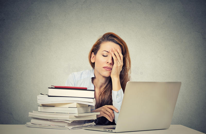 Jovem mulher sonolento cansado que senta-se em sua mesa com os livros na frente do computador foto de stock