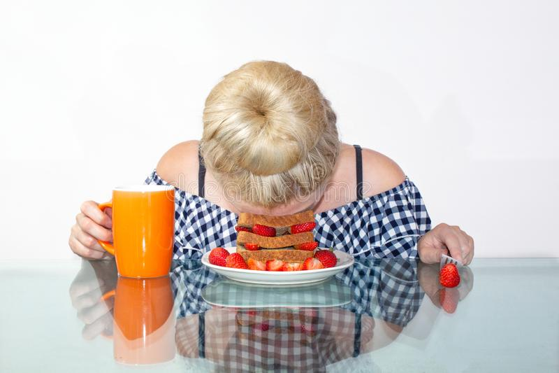 A jovem mulher sonolento comeu o café da manhã e pôs sua cabeça em uma placa, caiu adormecido em uma placa O conceito do amanhece imagens de stock royalty free