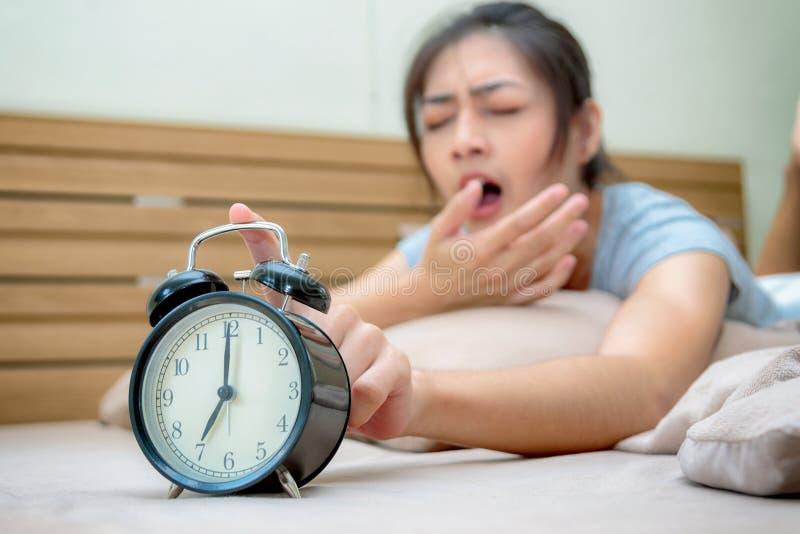 Jovem mulher sonolento na cama com mão de alargamento fechado dos olhos ao ala fotos de stock