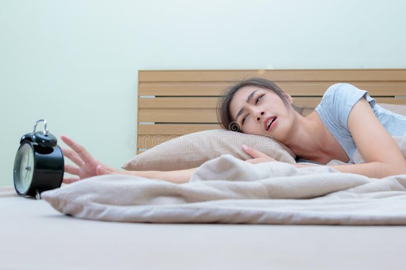 Jovem mulher sonolento na cama com mão de alargamento fechado dos olhos ao ala imagens de stock royalty free