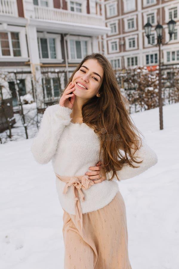 Jovem mulher surpreendente alegre bonito com cabelo moreno longo na camiseta de lã branca, saia leve andando na rua no inverno imagem de stock royalty free