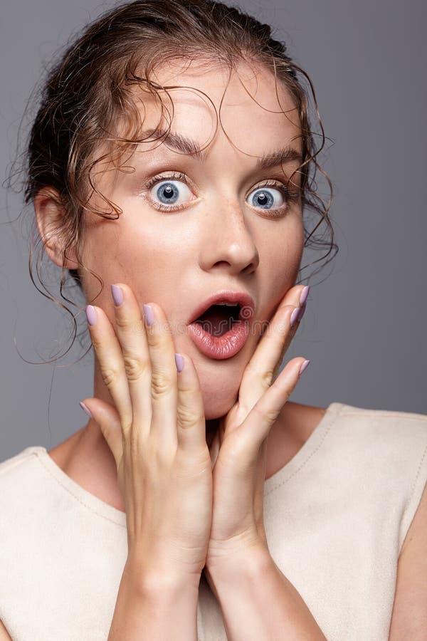 Jovem mulher surpreendida com mãos perto da cara e da boca abertas fotos de stock royalty free