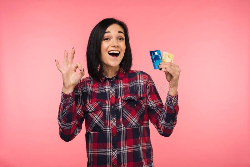 A jovem mulher surpreendida feliz alegre com exibição do cartão de crédito canta está bem sobre o fundo cor-de-rosa imagens de stock royalty free