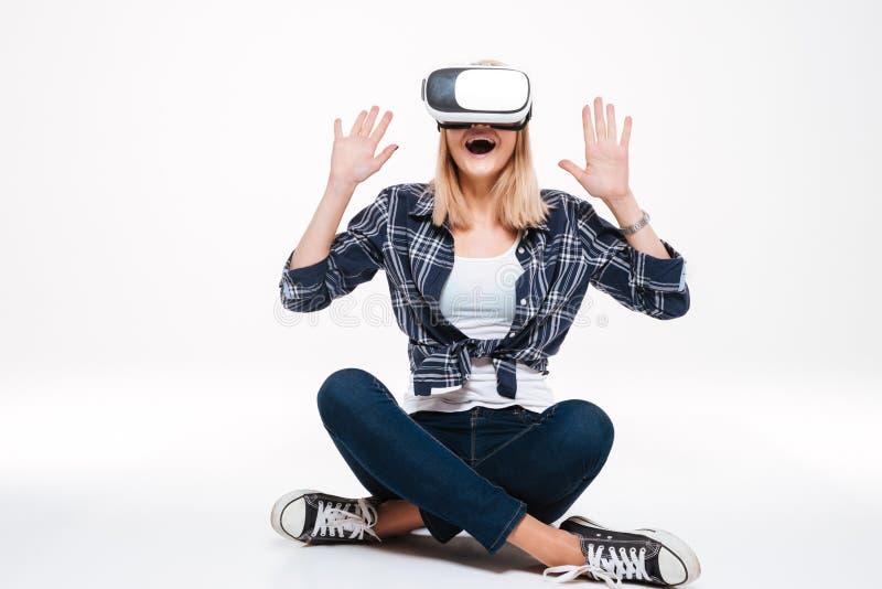 Jovem mulher surpreendida feliz que senta-se no assoalho que veste vidros de VR fotografia de stock royalty free