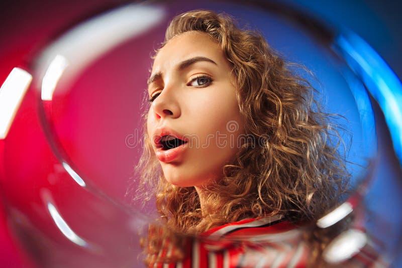 A jovem mulher surpreendida na roupa do partido que levanta com vidro do vinho fotos de stock royalty free