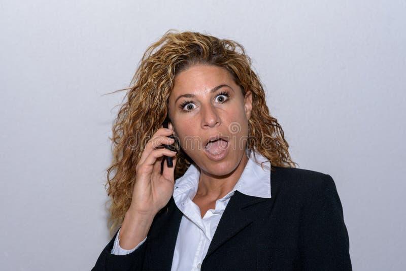 Jovem mulher surpreendida que conversa em seu móbil foto de stock