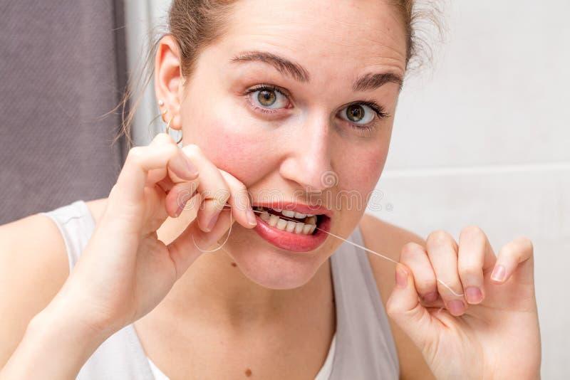 Jovem mulher surpreendida que guarda os dentes de inquietação e de limpeza de fio dental fotos de stock royalty free