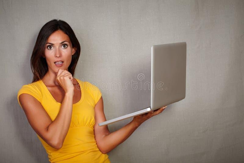 Jovem mulher surpreendida que guarda a tecnologia móvel foto de stock