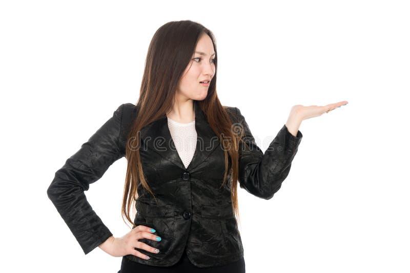 Jovem mulher surpreendida que mostra o produto com a palma aberta da mão fotos de stock royalty free