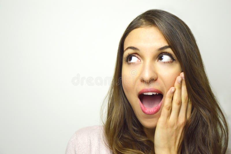 Jovem mulher surpreendida que olha ao lado com a boca aberta com mão na cara no fundo branco Menina entusiasmado que olha ao s fotos de stock royalty free