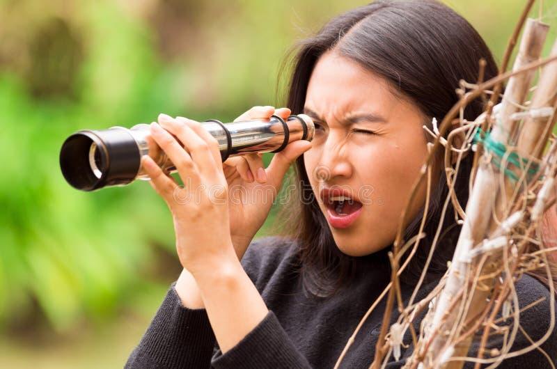 Jovem mulher surpreendida que olha através do monocular preto na floresta em um fundo borrado fotos de stock royalty free