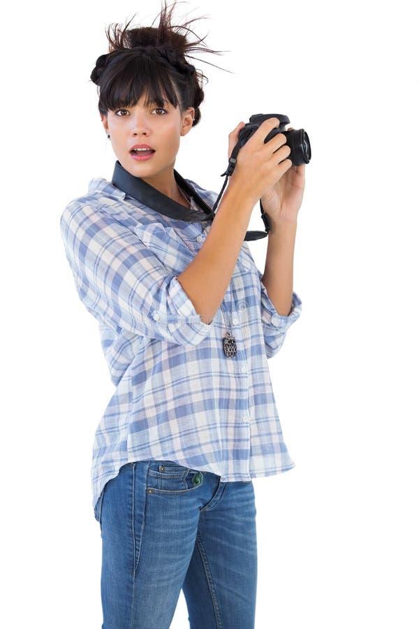 Jovem mulher surpreendida que toma a imagem com sua câmera fotos de stock