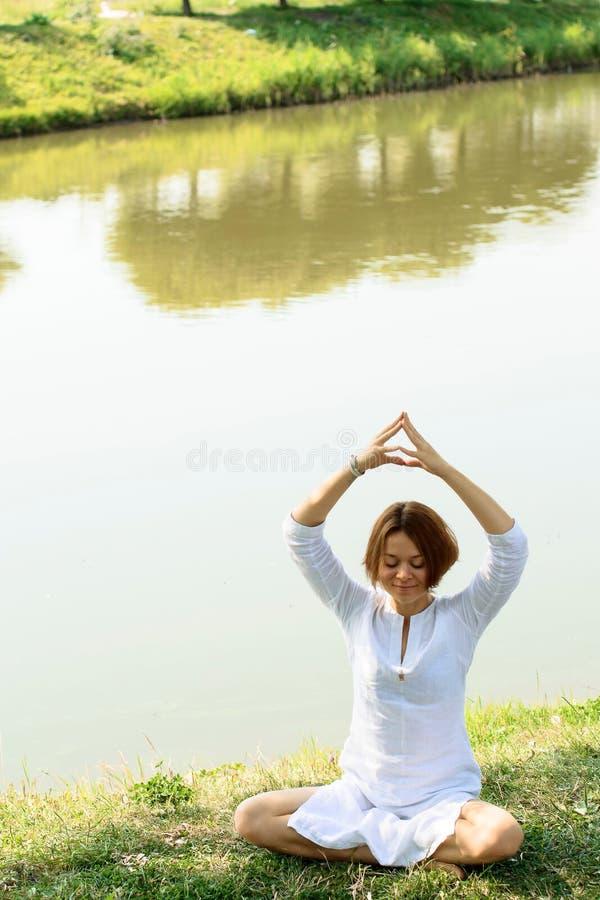 A jovem mulher tem a meditação da manhã no lugar pitoresco foto de stock