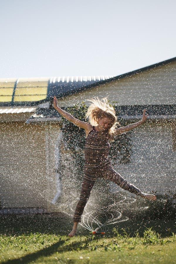 A jovem mulher tem o divertimento com um pulverizador da água fotografia de stock