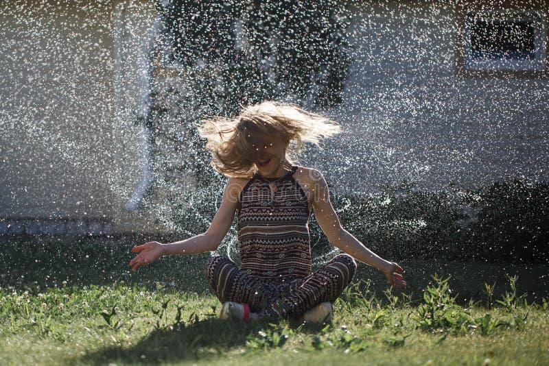 A jovem mulher tem o divertimento com um pulverizador da água foto de stock