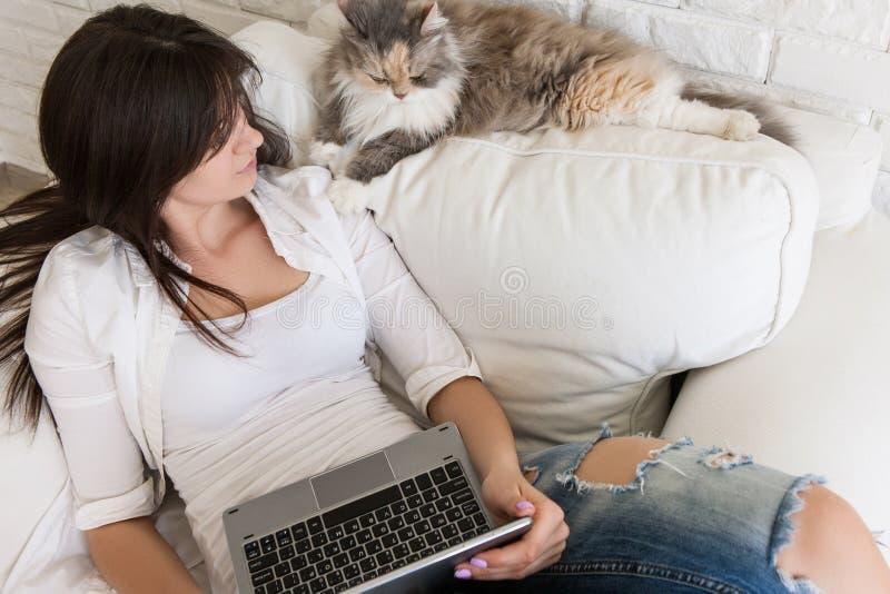 A jovem mulher tem o resto com seu gato fotografia de stock royalty free