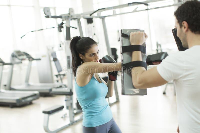 A jovem mulher tem um treinamento do encaixotamento com o instrutor no gym foto de stock royalty free