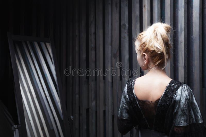 A jovem mulher tenta sobre o vestido imagens de stock royalty free