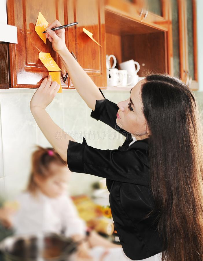A jovem mulher tenta trabalhar em casa com um beb? pequeno de grito fotografia de stock royalty free