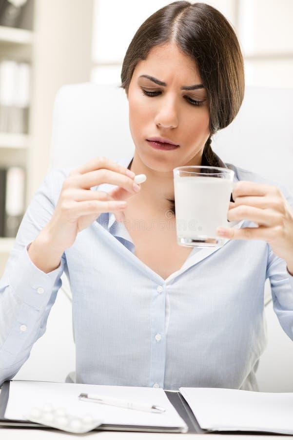 A jovem mulher toma um comprimido no trabalho imagem de stock royalty free