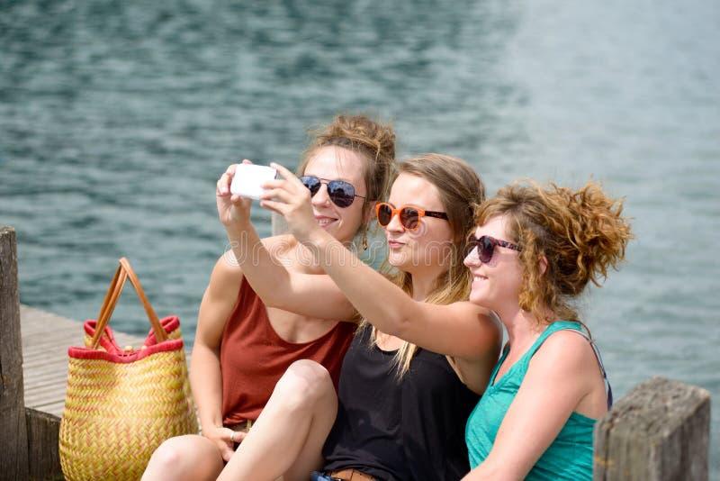 Jovem mulher três na praia com seu telefone foto de stock