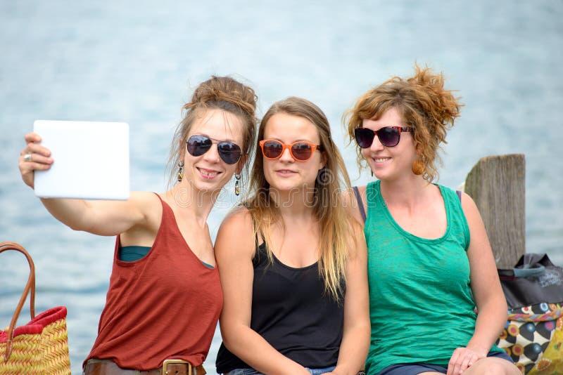 Jovem mulher três na praia com sua tabuleta digital foto de stock